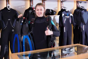 Female is standing in full set of  diving equipment