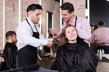 Two hairdressers making hairstyle for female client