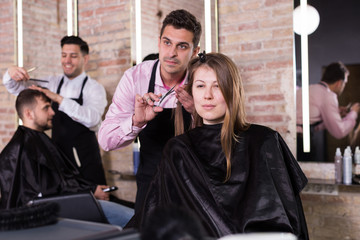 Brunette getting haircutting in salon