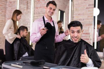 Satisfied man approving result of hairdresser work