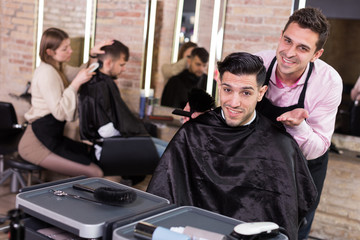 Hairstylist and satisfied male customer after haircut