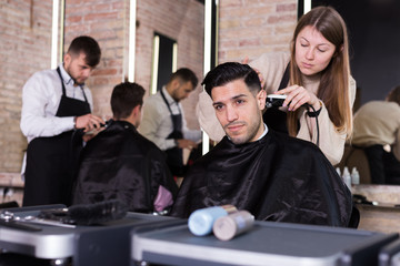 Hairdresser doing styling of guy with electric hair clipper