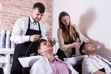 Hairdressers washing hair of clients