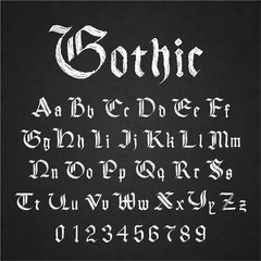 Old hand drawn gothic letters drawing with white chalk on black chalkboard