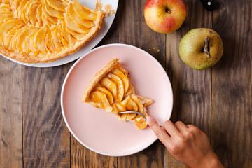 Child hand eating a portion of apple tart