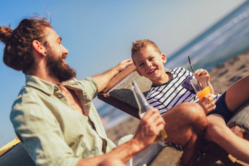 Father and son having fun at beach together portrait fun happy lifestyle