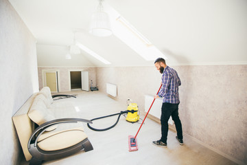 Young bearded man makes cleaning the house