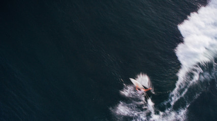 bali indonesia vertical aerial drone shot early morning and a surfer one moment in surf