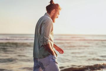 One man walking on the beach on sunset.