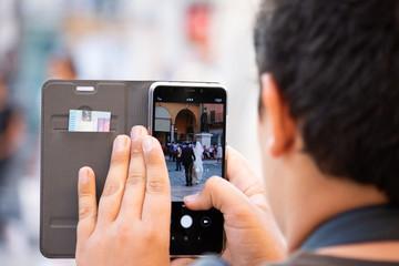 Ragazzo che fotografa la sposa e lo sposo con lo smartphone