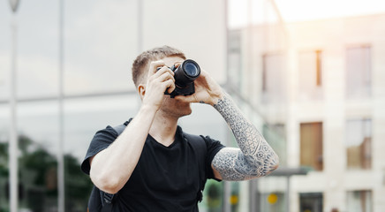 Attractive man making photos outdoors at cityscape background