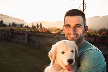 Young man with puppy dog in arms