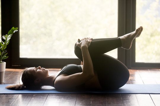 Young sporty woman practicing yoga, doing Knees to Chest exercise, Apanasana pose, working out, wearing sportswear, grey pants and top, indoor full length, yoga studio