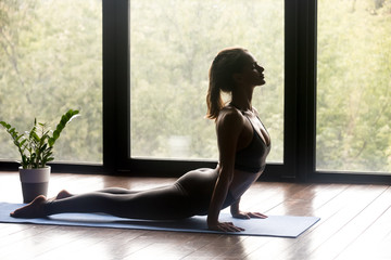 Young sporty woman practicing yoga, doing upward facing dog exercise, Urdhva mukha shvanasana pose, working out, wearing sportswear, grey pants and top, indoor full length, yoga studio