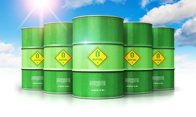 Group of green biofuel drums against blue sky with clouds and sun light