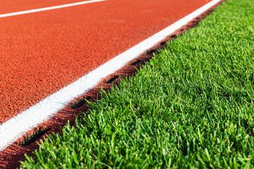 Photo sur Aluminium Stade de football Red running track and green grass field at the sport stadium