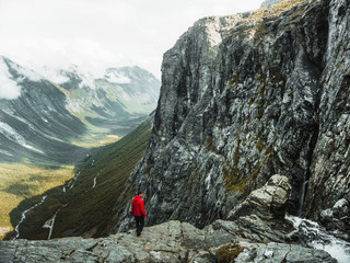 Active hiker hiking, enjoying the view, looking in Norway mountain landscape. Mountaineering sport lifestyle concept