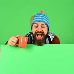 Man in warm hat holds brown cup on green background