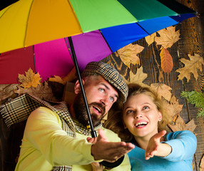 Rainy weather not obstacle for them. Couple dating. Hipster with beard and cheerful girl expect rainy weather hold colorful umbrella. Man bearded and blonde woman lay on wooden background top view