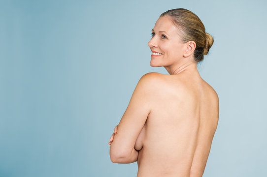 Mature naked woman standing