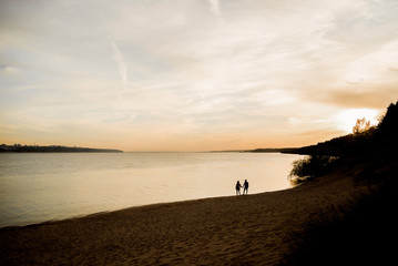 Two lovers stroll along the river at sunset.