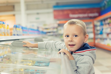 A child, a small boy 5-7 years old, opens a cold store in a supermarket.