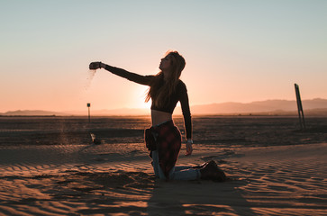 Side view of young woman kneeling touching and throwing the sand in a desert sunset background