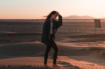 Rear view of young woman walking by the sand of desert to the sun in a sunset