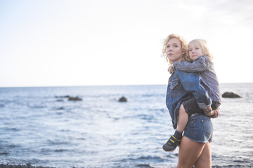 beautiful young mother and little child blonde too walking at the beach in happiness. enjoying the outdoor activity and stay in love. the woman carry the little kid and both laugh and smile