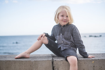 Little blonde beautiful boy pose in front of the camera outdoor with casual clothes and nice smile. blue sea in background