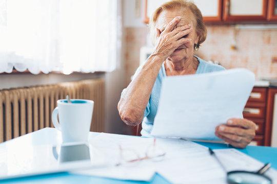 Elderly woman looking at her utility bills