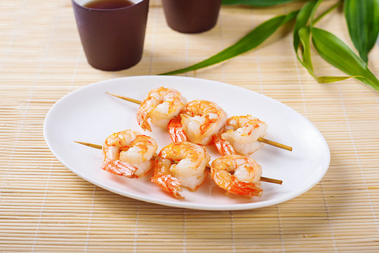 Close-up of barbecue shrimp skewers on a white plate in the restaurant.