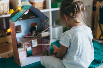 Portrait of adorable little girl playing with toy house at home