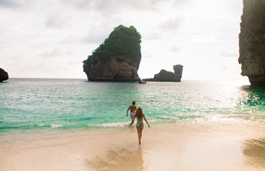 Young couple running to the sea at a beach in Koh Phi Phi, Thailand