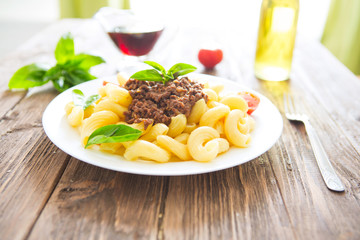 Plate of penne pasta bolognese on wooden table