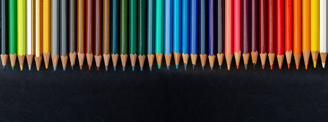 Colored pencils texture. Foreground. All the range of colors of the rainbow. Start of school Beautiful wallpaper. Isolated on black background.