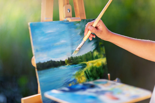Young pretty woman artist draws paints a picture of a lake on open plain air outdoors