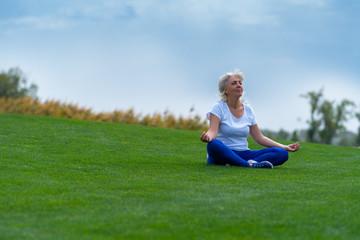 Senior woman meditating on green grass
