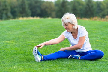 Senior woman stretching on green grass in park