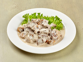 Beef in cream sauce with lettuce leaves.