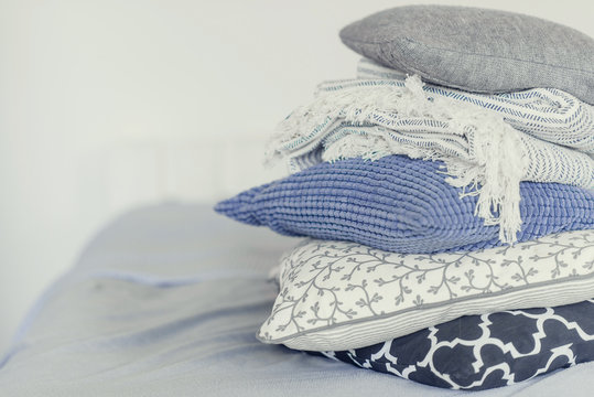 pile of pillows on the edge of the bed, in gray, monochrome