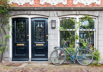 Typical house entrance with two doors, window, and bicycle in the old town of Amsterdam, Netherlands