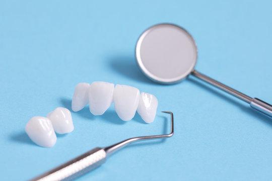Zircon dentures samples on a blue sheet with dental tools - Ceramic veneers - lumineers