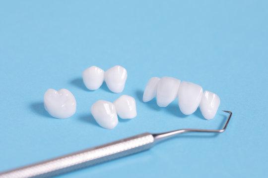 Dental explorer tool with zircon dentures on a blue sheet - Ceramic veneers - lumineers
