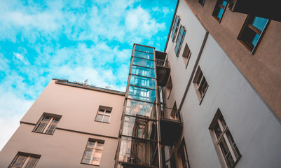 glass elevator at apartment house with fluffy background sky