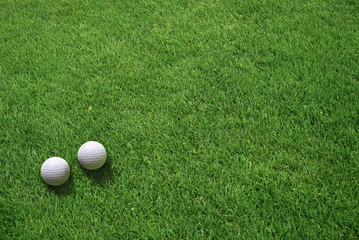 Top View of Two White Golf Balls Lying on Green Grass