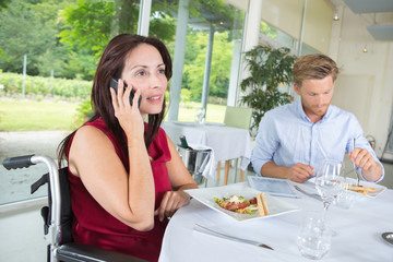 Disabled lady on telephone while dining with man