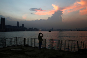 A man takes a photo during sunset at Lei Yue Mun in Hong Kong