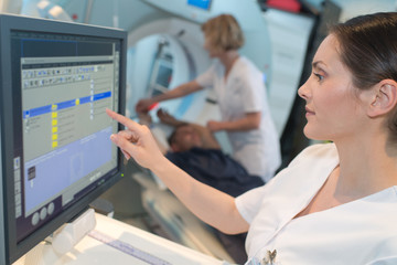 female doctor pushing control button on ct scanner