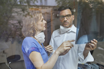 Portrait of radiologist and nurse behind windowpane looking at x-ray image